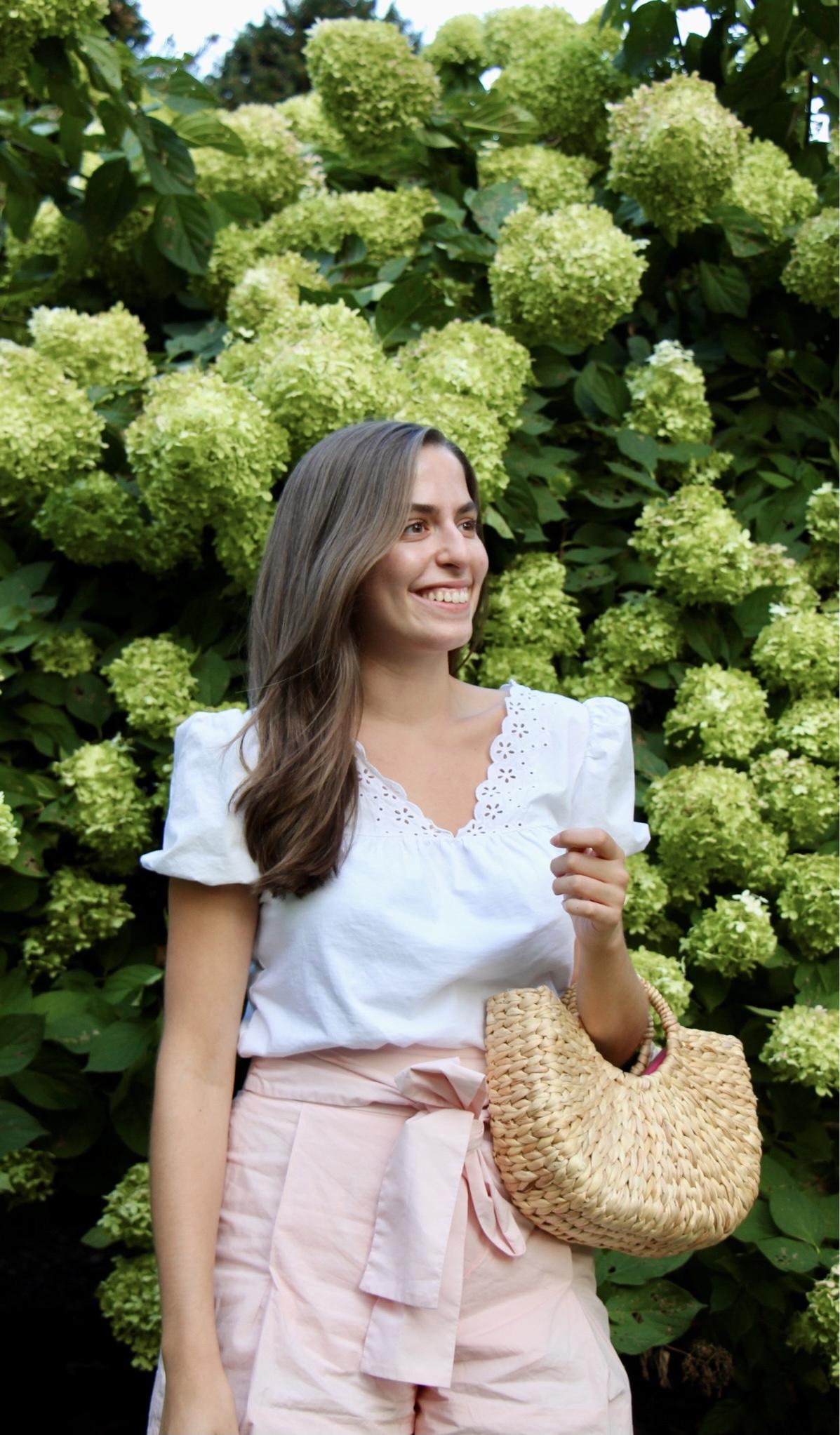 pink shorts, white puff sleeve top, straw bag, hydrangeas