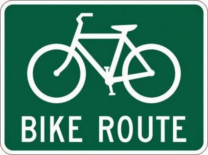 White-against-green roadway sign displaying a bicycle in profile above the caption, 'Bike Route.'