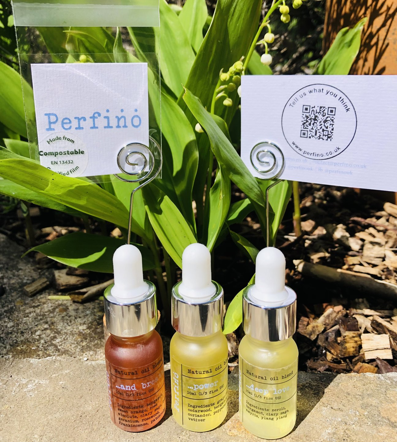 three bottles of natural essential oil blends from Perfino all lined up on the ground in front of plants