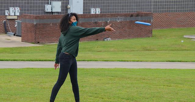 woman throws frisbee