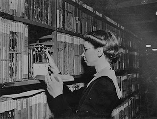 [Archivist (Adelaide Minogue) checking humidity stacks, August 12, 1942. US National Archives [Public domain], via Wikimedia Commons]