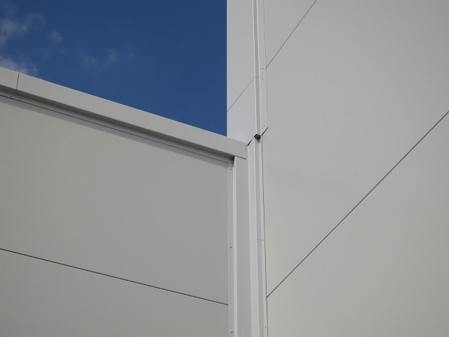 Corner on outside of white, plastic-clad building.