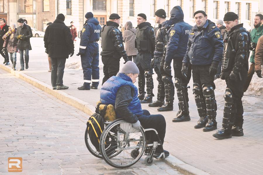 Vīrietis ratiņkrēslā mēģina uzbraukt uz gājēju celiņa pāri augstai ceļa apmalei bruņās satērpto policistu priekšā