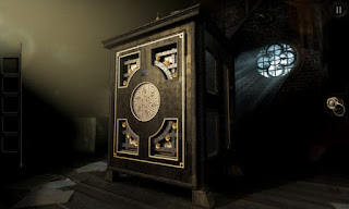An intricate wood and brass puzzle box on a table in the attic in front of a round window