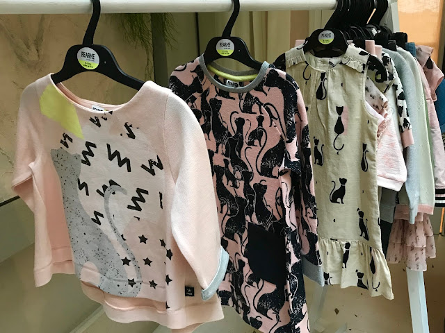 A peachy pink t-shirt with a large cat, a pink dress with black cat prints and a linen style cream dress with cat prints