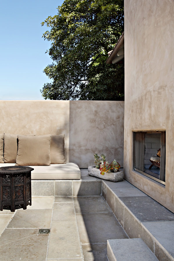 Outdoor living with beautiful built-in sofas and fireplace at Provence style home of architect William Hefner. #outdoorliving #fireplace #FrenchCountry #Provence #Provencal #stucco