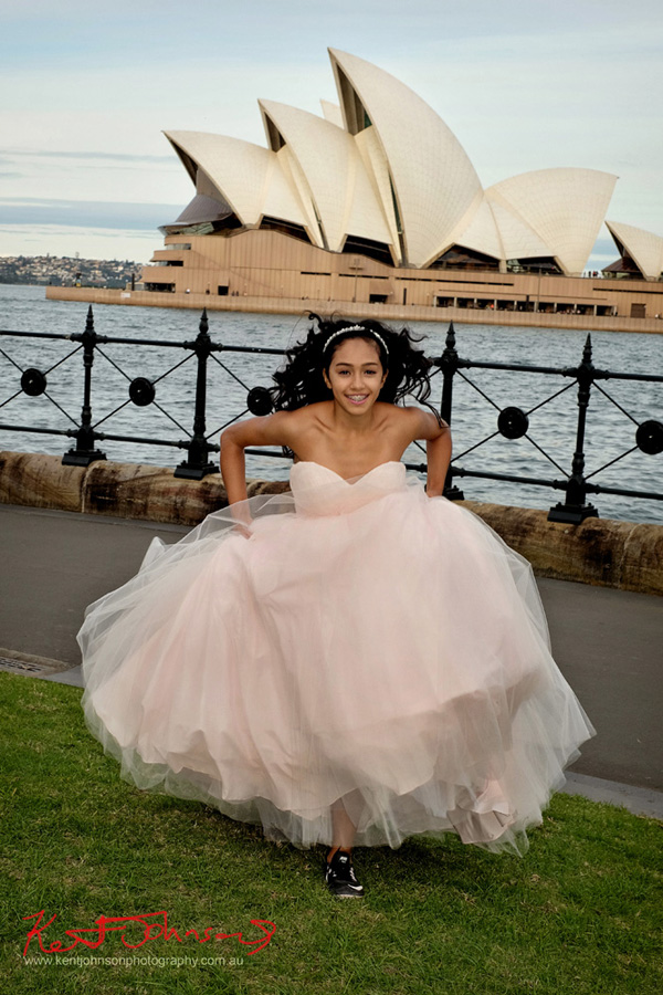 Running in track spikes wearing the Special XV Quinceañera dress in front of the Sydney Opera House for a sweet 15 Birthday portrait. Photography by Kent Johnson.