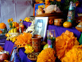 A view of a colorful ofrenda. There is a black and white portrait in the middle with many yellow flowers and food on a purple cloth.