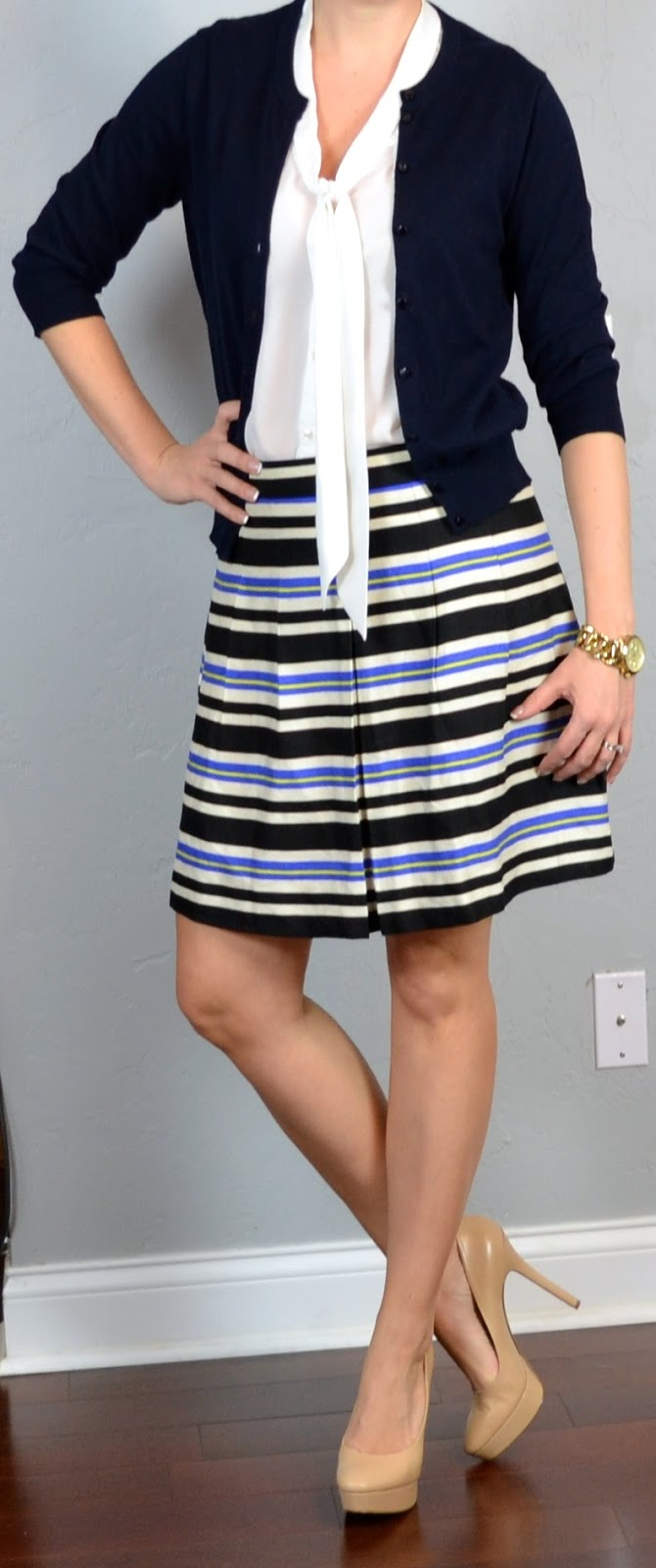The top features a mid-width navy blue and white horizontal striped design. A solid colored navy blue skirt has been added to the dress just above the natural waistline area. A stretch band of navy blue fabric compliments the waist.