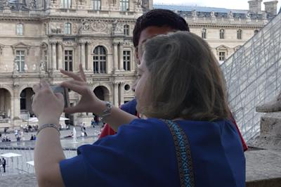 سائحان في ساحة اللوفر في باريس