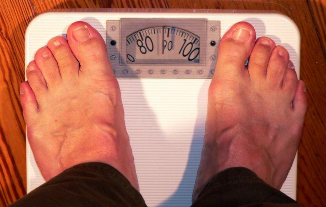 Uomo grasso che si pesa sulla bilancia