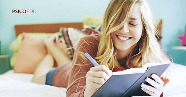 Mulher jovem escrevendo diário carta em cima da cama