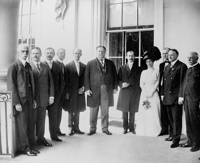 Wilbur (left of center) and Orville Wright (right of center) posed on either side of U. S. President William Howard Taft (center), with Katharine Wright is to the right of Wilbur; others in group are unidentified.  Portico of the White House, Washington, D. C.