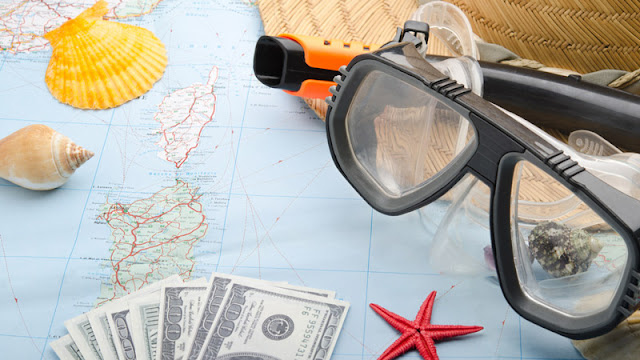 a paper map being covered by seashells, money, and a snorkel