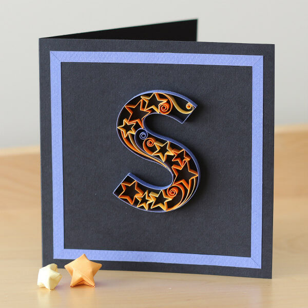 Quilled letter S filled with paper stars and scrolls on a greeting card
