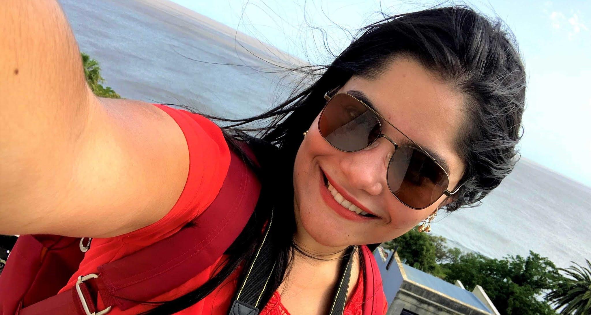 selfie mulher jovem com oculos escuros, cabelo preto, morena e blusa vermelha