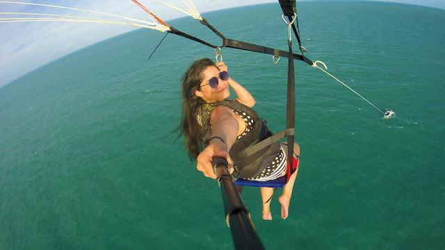 mulher com um paraquedas e sentada em uma cadeirinha puxada por uma lancha no mar