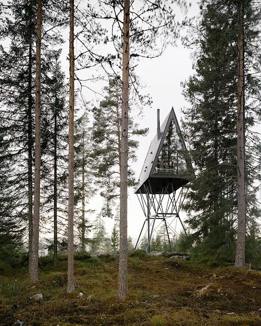 cabaña elevada al fondo con árboles al frente