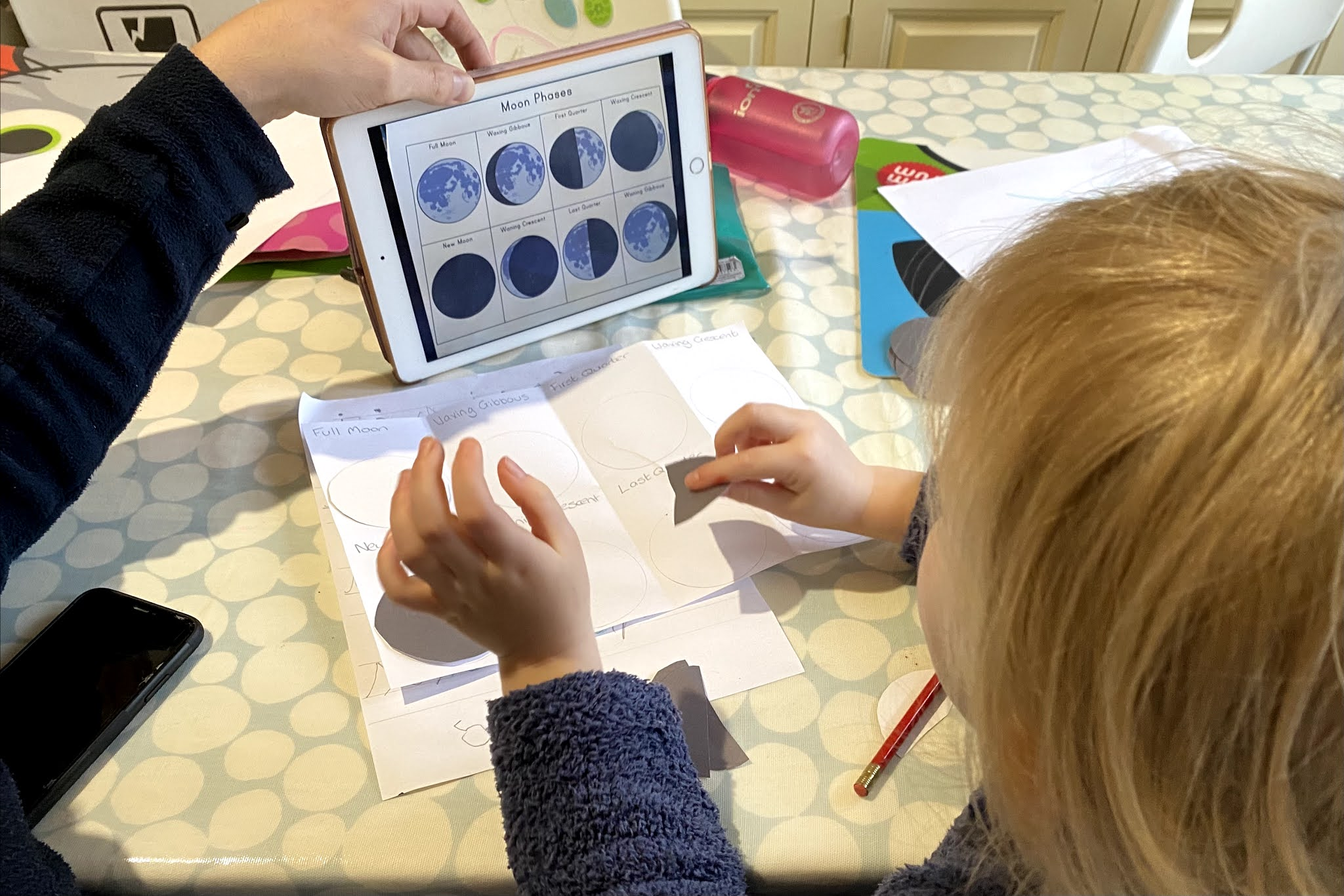 A parent holding an iPad and sitting with a child talking through stages of the moon