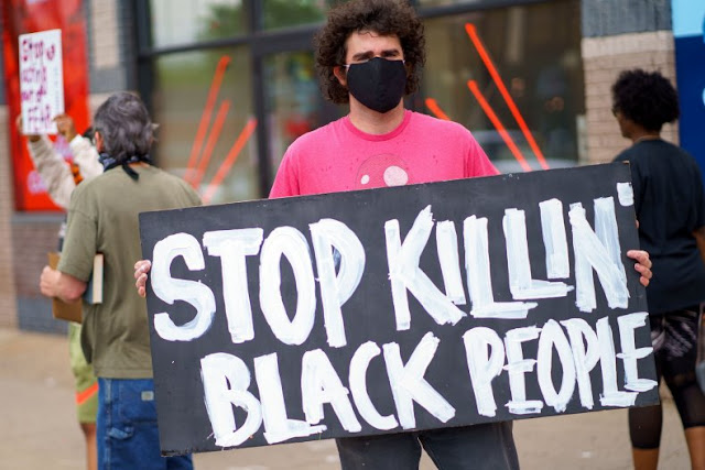 while man wearing mask holding a sign that reads stop killing black people