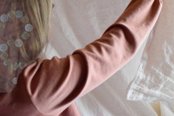 Nainen ihailee Omin mitoin -ompeluohjeen mukaan ommeltua pussilakanaa.