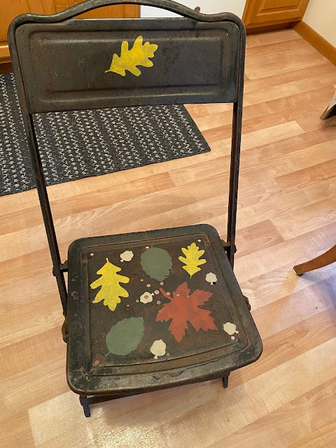 Photo of a stenciled rusty folding chair.