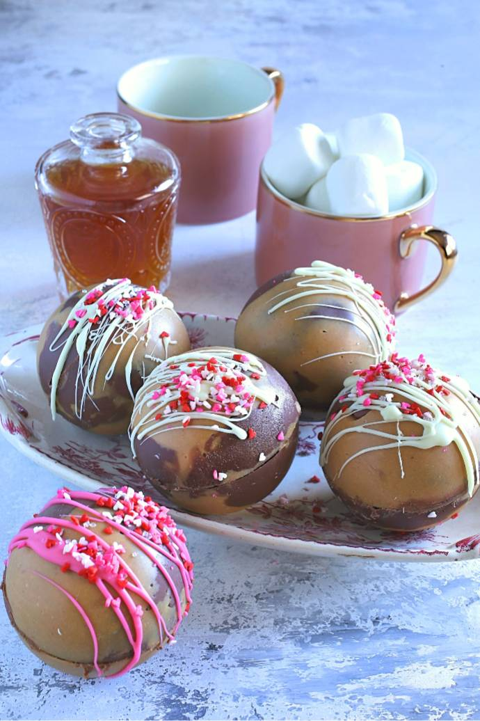 Recipe for hot cocoa bombs made with a marbled peanut butter and milk chocolate shell, filled with hot cocoa mix and bourbon.