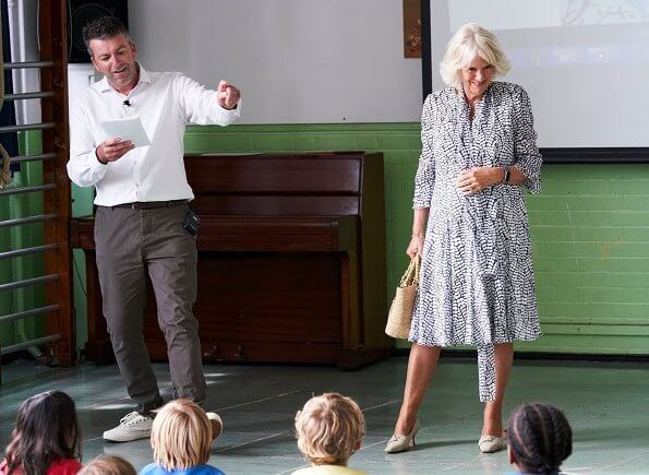 The Duchess of Cornwall is patron of The National Literacy Trust. The duchess wore a printed silk summer midi dress. beige pumps and bag