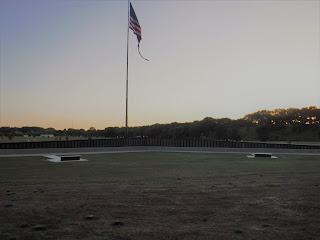 the Vietnam War Memorial Wall at Freedom Park is visible at sunset with a large flag behind it and green space all around