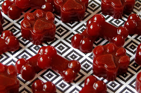 Deep red beetroot and carob gelatin gummy dog treats shaped like paws and bones