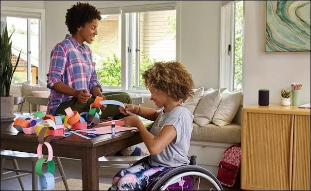 Una niña pequeña en silla de ruedas haciendo manualidades con su mamá en una mesa con un Amazon Echo cerca.