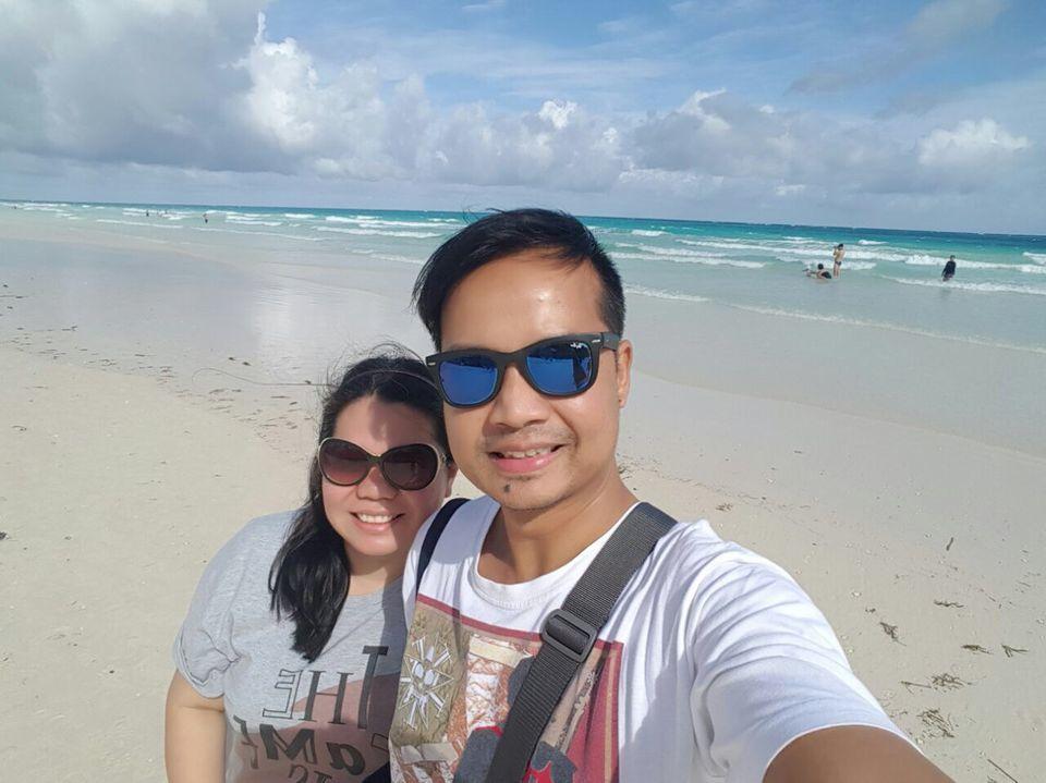 A couple strolling along white beach in Boracay