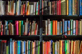Estantería de una librería con libros ordenados de colores