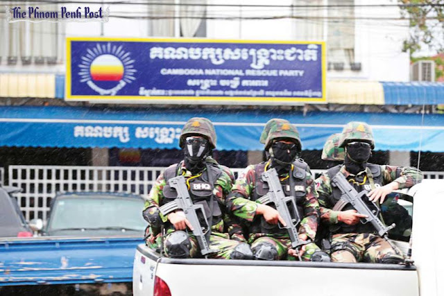 Masked, heavily armed members of the Prime Minister's Bodyguard Unit sit in a truck outside CNRP party headquarters yesterday in Phnom Penh. Hong Menea