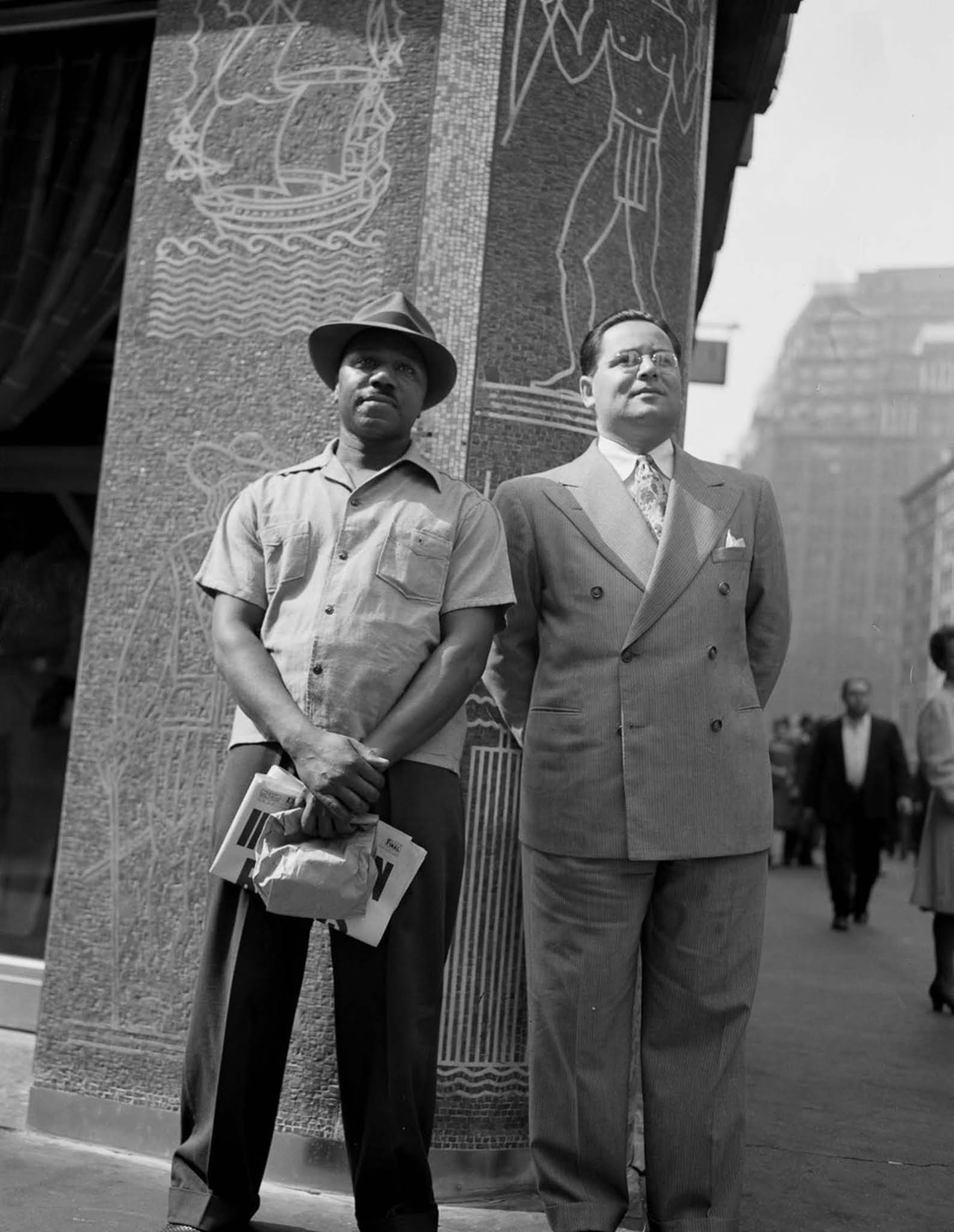 Two men stand tersely on a street corner on the day that news broke.