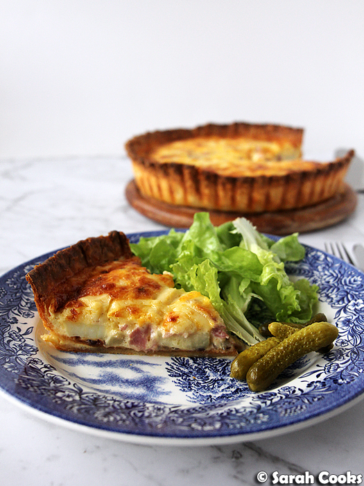 Slice of raclette tart with salad and cornichons