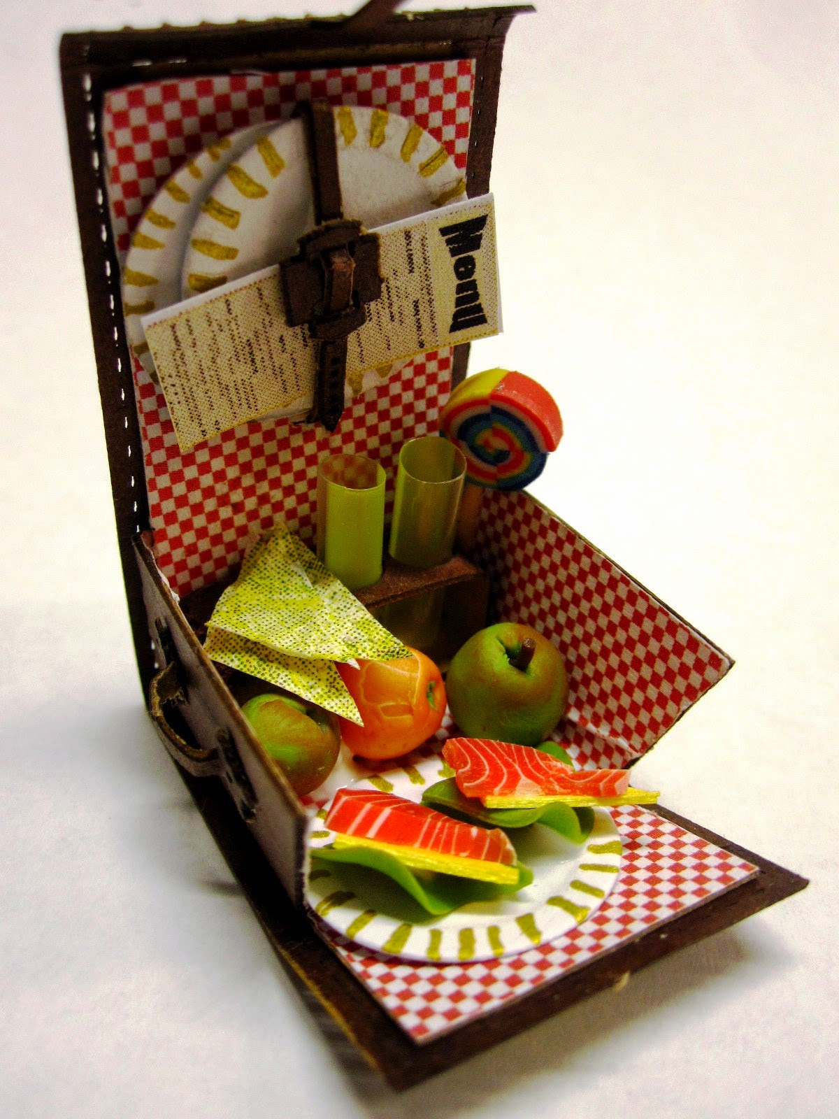 A miniature picnic hamper with red checked lining, holding two glasses, a lollipop, two smoked salmon and lettuce sandwiches, two apples and an orange.