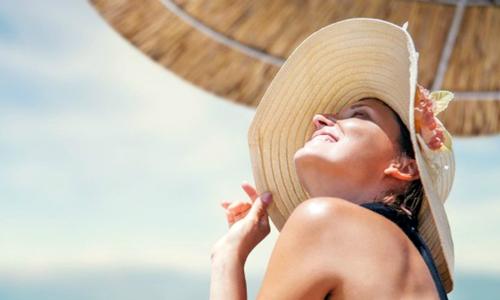 Chica guapa en la playa con sombrero
