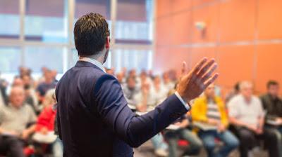 A man speaking in public, huge crowd
