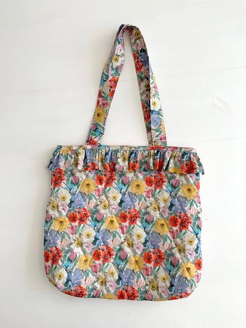 Liberty stoffet tasken er syet i er dejligt sommerligt i farverne.