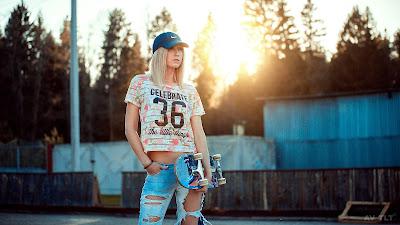 Chica con gorra y skate en la plaza mirando a la nada
