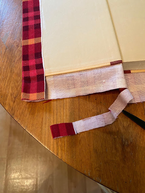 Photo of covering a hardcover book with plaid flannel.