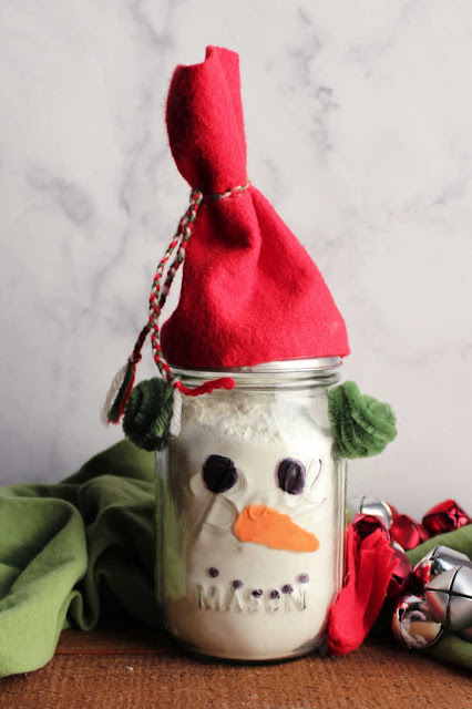 glass jar decorated like a snowman and filled with white hot chocolate mix