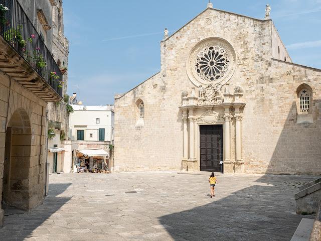 Plaza de Otranto con una niña corriendo frente a la iglesia