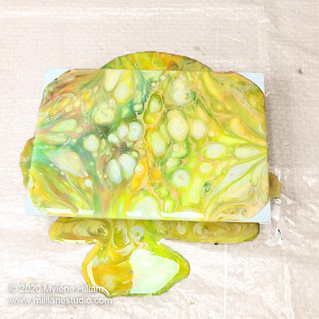 Dirty resin pour in shades of yellow and green with white cells done with casting resin and flowing straight off the canvas