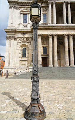 Photograph of an elaborate cast-iron lamp post in front of the west facade of the cathedral. Its appearance is described more fully in the text.