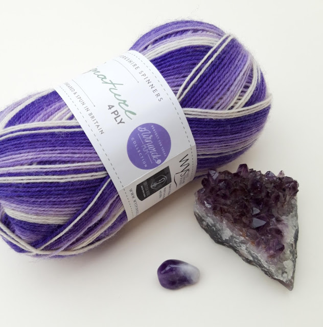 A flatlay of a ball of purple Hidden Gem yarn, an amethyst tumblestone and an amethyst geode
