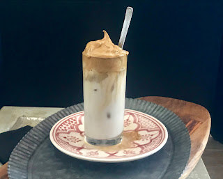 Tall glass of whipped or dalgona coffee, iced, with spoon