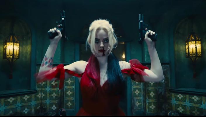 Imagem: a Arlequina, interpretada por Margot Robbie, com cabelos loiros e longos caindo pelos ombros e tingidos de vermelho e preto nas pontas, usando um vestido vermelho rasgado em algumas partes, erguendo as mãos com duas pistolas, em um tipo de sala ou corredor decorado com azulejos verdes e com abajures acesos.