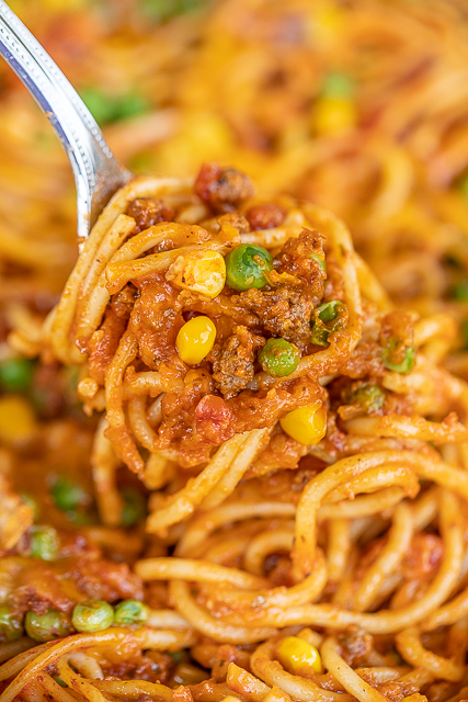 baked spaghetti with corn and peas on a fork